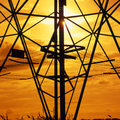 Power and light a ray of the sun blinks through the steelwork of an electricity pylon Royalty Free Stock Photos