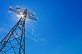 Power line with sun a high voltage pylons against blue sky and rays Royalty Free Stock Images