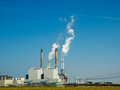 Power plant against a blue sky with fumes Royalty Free Stock Photography