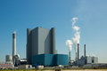 Power plant against a blue sky with fumes Stock Photos