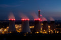 Power plant at night scene with huge coal smokestacks illuminated with red lamps making blurred effect on smoke Stock Photo