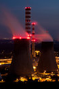 Power plant smokestacks at night detailed view of a few big on coal facility during blurred effect of smoke illuminated by red Royalty Free Stock Photo