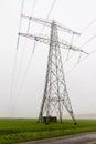 Power pylon field foggy morning netherlands Royalty Free Stock Images
