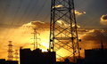 Power transmission line towers stand under blue sky with beautiful sunset in the background Stock Photos