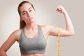Powerful woman measuring her biceps with a yellow measuring tape Stock Photo