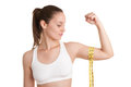 Powerful woman measuring her biceps with a yellow measuring tape Royalty Free Stock Photo