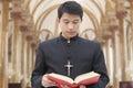 Präst looking down på bibeln i en kyrka Royaltyfria Bilder