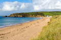 Praa sands cornwall england near penzance and mullion on the south west coast path with a sandy beach blue sky on a beautiful Royalty Free Stock Photo