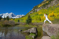 Practicing yoga at maroon bells in autumn a happy woman the scenic fall as a backdrop Stock Photo
