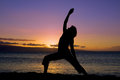 Practicing yoga at sunset a woman doing silhouetted in the on the beach Stock Photo