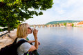 Prague, Czech Republic. Female traveler drinking coffee and enjoying a panoramic view.