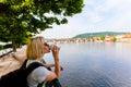 Prague, Czech Republic. Female traveler drinking coffee and enjoying a panoramic view.