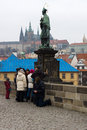Prague sculpture of john of nepomuk on charles bridge beggar near tourists czech republic february the is a famous Stock Photos
