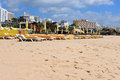 Praia da rocha loungers and parasols for shade along the golden sandy shored beach of with resort buildings in the background in Stock Photography