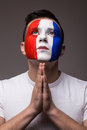 Pray France football fan in game of France national team look at sky. Royalty Free Stock Photo