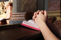 Prayer in a church and book or the scripture close up of female hands Royalty Free Stock Photo
