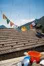 Prayer flags on a roof with a blue sky and some pieces of ordinary house hold equipments scareno italy Stock Images