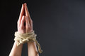 Prayer for freedom two hands of a young woman in position tied with a rope Royalty Free Stock Photos
