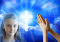 Prayer girl child hands a montage of a young praying and cross in the sky Royalty Free Stock Image