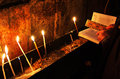 Prayer with Holy Bible and candles in the church. Stock Photos