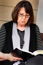 Prayer warrior reads bible a dark haired senior citizen lady sitting peacefully reading a shallow depth of field Royalty Free Stock Photos