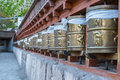 Prayer wheels prayer s rolls of the faithful buddhists line of many religious prayers on wooden rack side view with grey Royalty Free Stock Images