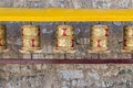 Prayer wheels prayer s rolls of the faithful buddhists line of many religious prayers on wooden rack side view with grey Stock Image