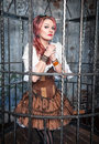 Praying beautiful steampunk woman in the cage with pink hair standing metal Royalty Free Stock Images