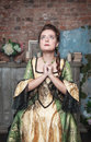 Praying beautiful woman in medieval dress the old room Royalty Free Stock Image