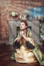 Praying beautiful woman in medieval dress the old room Royalty Free Stock Images