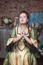Praying beautiful woman in medieval dress the old room Stock Photo