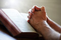 Praying hands on a holy bible folded in prayer in church concept for faith spirtuality and religion Royalty Free Stock Photography