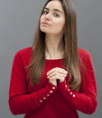 Praying and happiness concept for pious s girl with both hands flat on her chest with warmth faith in church trust in Stock Photo