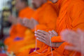 Praying monk hand holding holy rope Stock Photos