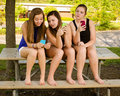 Pre teen girls texting while hanging out in front young of their school Royalty Free Stock Photography