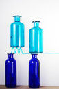 Precarious equilibrium two light blue glass bottles on a straw being supported by other two blue bottles so they are in a Royalty Free Stock Photos