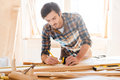 Precision throughout serious young male carpenter working with wood in his workshop Royalty Free Stock Photography