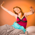 Preety woman stretching arms after waking up in early morning cosy bedroom Royalty Free Stock Photos
