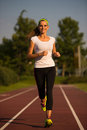 Preety young woman running on a track summer afternoon Royalty Free Stock Photo
