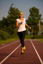 Preety young woman running on a track summer afternoon Stock Image