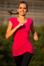 Preety young woman running on a track summer afternoon Stock Photo
