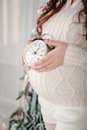 Pregnancy closeup of a pregnant woman holding an alarm clock near her belly against christmas tree Stock Image