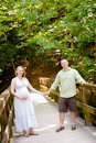 Pregnancy a couple walking outside happy young expecting baby holding hands on wooden bridge Stock Photography