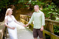 Pregnancy happy coulple outside young couple expecting a baby holding hands on a wooden bridge Royalty Free Stock Images