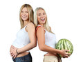 Pregnancy. One woman is holding pregnant belly, other woman is holding watermelon. Isolated. Two happy girls laughing. Royalty Free Stock Photo