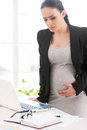 Pregnancy pains and aches depressed pregnant businesswoman touching her abdomen while standing near her working place in office Stock Photo