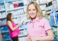 Pregnancy and pharmaceutics pharmaceutist with pregnant on background at store theme smiling female worker portrait women choosing Royalty Free Stock Images