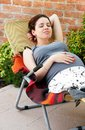 Pregnancy relaxed happy smiling pregnant young caucasian woman lying in chair outdoor Stock Image