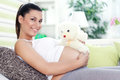 Pregnancy with teddy bear smiling pregnant woman lying on couch Royalty Free Stock Images