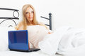 Pregnancy woman awaking with laptop on white sheet in her bed at home Stock Photos